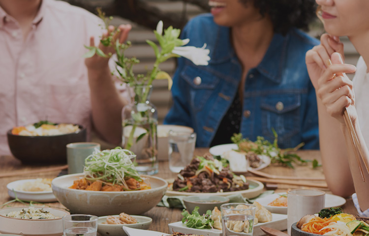Images of people of various nationalities sitting around a table with Korean food