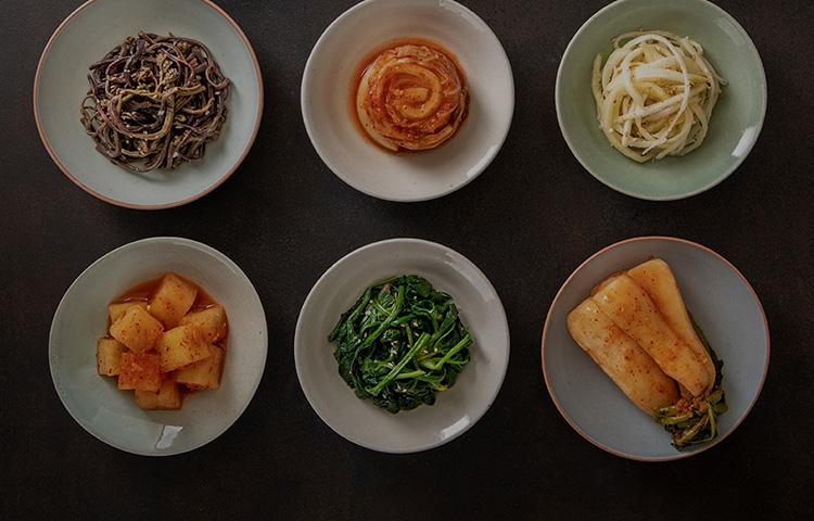 한국 음식이 놓인 테이블에 둘러 앉은 다양한 국적의 사람들 이미지
