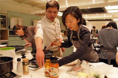 쿠킹클래스에 참가한 여성이 조리대에서 조리를 하고 있고 요리사가 그녀를 도와주고 있다. 뒤로는 다른 참가자들의 모습이 보인다.